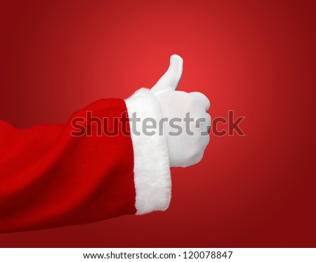 Santa Claus hand showing thumbs up over red background with copy space - stock photo