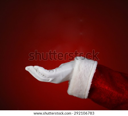 Santa Claus hand with his palm facing up over a light to dark red background. Closeup showing only his hand and arm. - stock photo