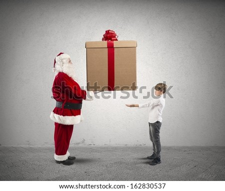 Santa Claus handing a big present for a child - stock photo