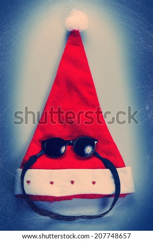Santa Claus hat and sunglasses on a dark background - stock photo