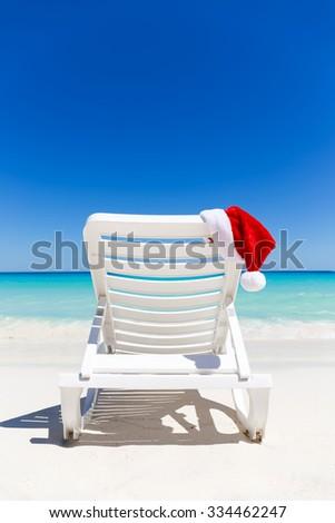 Santa Claus Hat on sunbed near  sandy beach with turquoise caribbean sea water. Tropical Christmas Card - stock photo