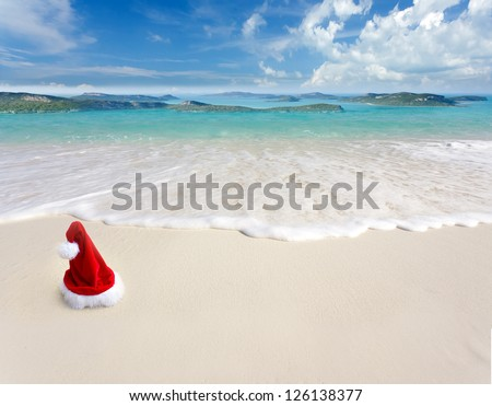 Santa Claus hat on white sand tropical beach. - stock photo