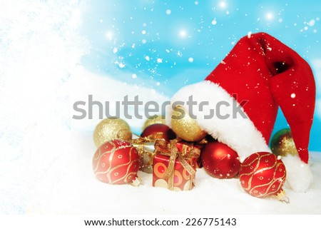 Santa Claus hat with Christmas balls and gift box on snow. - stock photo