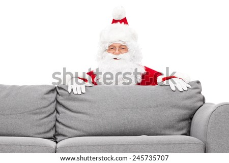 Santa Claus hiding behind a sofa isolated against white background - stock photo