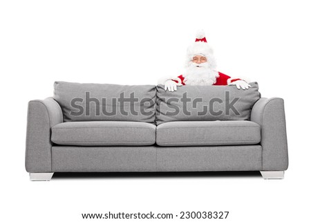 Santa Claus hiding behind a sofa isolated on white background - stock photo