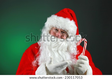 Santa Claus hold a Fresh Candy Cane while against a green background. Candy Canes are loved by everyone at Christmas Time around the world. Candy Canes are made with Peppermint flavor. Peppermint  - stock photo