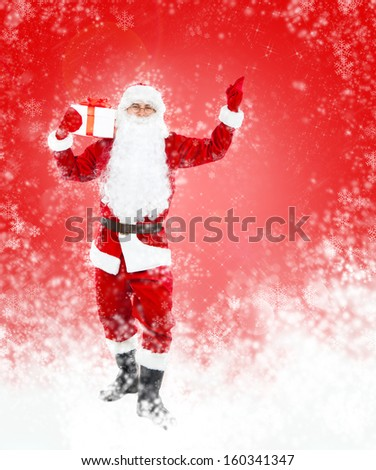 Santa Claus hold gift box present point finger glove up at copy space over red christmas background abstract winter snow, concept of christmas new year sale shopping - stock photo