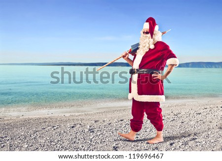 Santa Claus holding a beach umbrella on a beach - stock photo