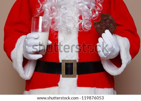 Santa Claus holding a glass of milk and a chocolate cookie. - stock photo