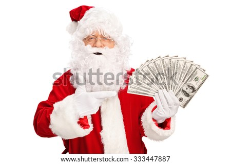 Santa Claus holding money in one hand and pointing towards them with the other isolated on white background - stock photo