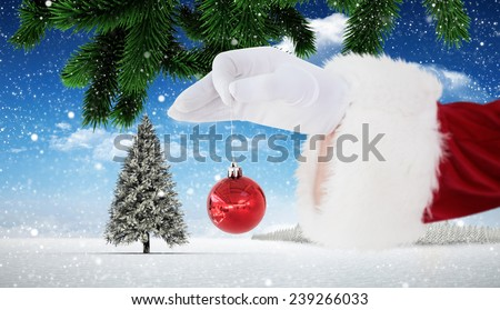 Santa claus holding red bauble against christmas scene - stock photo
