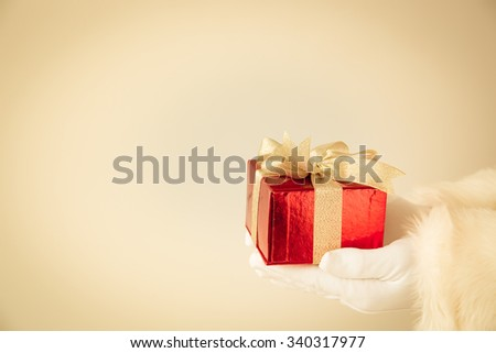 Santa Claus holding red gift box in hands. Christmas holiday concept - stock photo