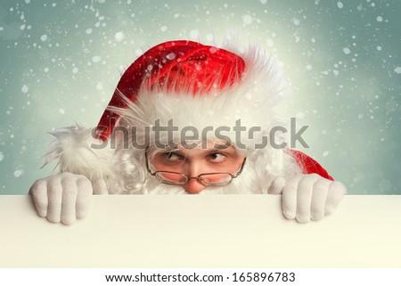 Santa Claus holding white blank banner looking around - stock photo