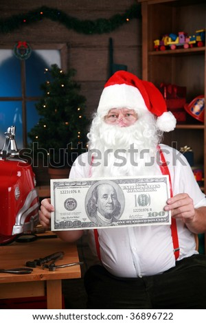 """Santa Claus holds a giant """"one hundred dollar bill"""" representing the high cost of christmas and the holiday season in general - stock photo"""