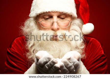 Santa Claus in eyeglasses blowing snow from his palms - stock photo