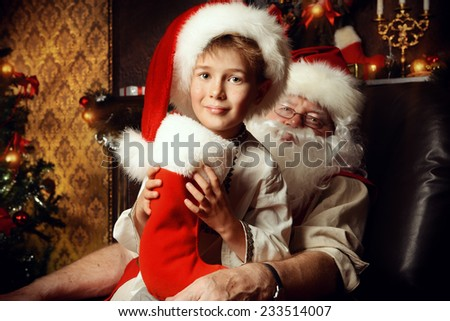 Santa Claus in his everyday clothes in Christmas home d�©cor. Happy little boy helps Santa Claus get ready for Christmas. - stock photo
