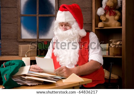 Santa Claus in his workshop reading letters and surrounded by toys and presents. - stock photo
