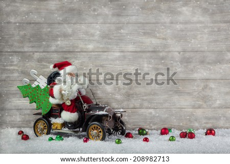 Santa claus in rush with his car: christmas shopping stress. Decoration with old vintage tin toys on wooden background. - stock photo