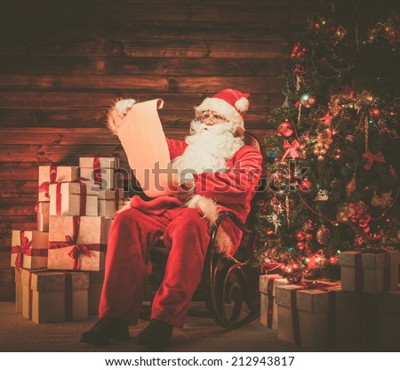 Santa Claus in wooden home interior reading wish list scroll - stock photo