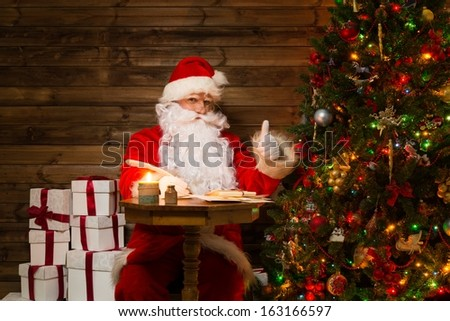 Santa Claus in wooden home interior sitting behind table and writing letters with quill pen - stock photo