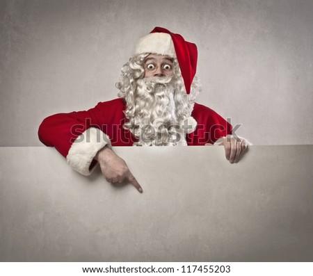 Santa Claus indicating something a white poster - stock photo