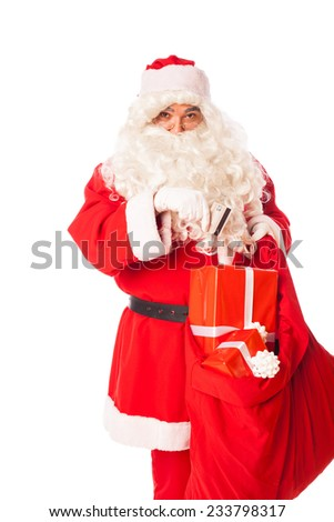 santa claus introducing a credit card in his sack of gifts, isolated - stock photo