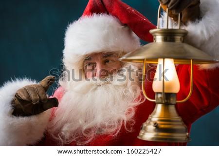 Santa Claus is holding a shining lantern outdoors at North Pole at night - stock photo