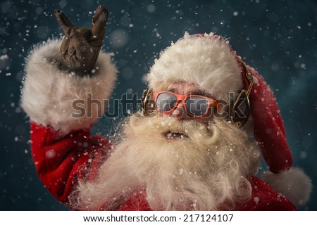 Santa Claus is listening to music in headphones wearing sunglasses. Christmas. - stock photo