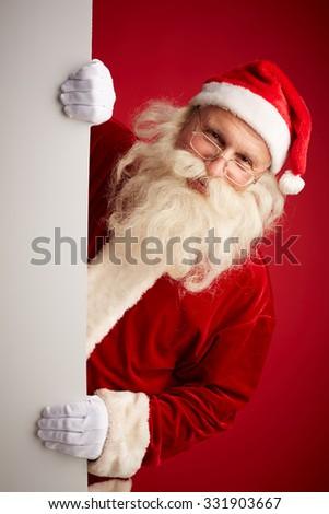 Santa Claus looking at camera out of billboard - stock photo