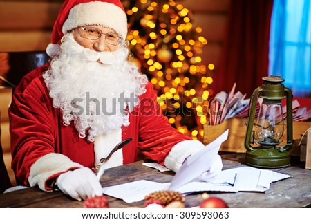 Santa Claus looking at camera while reading Christmas letter - stock photo