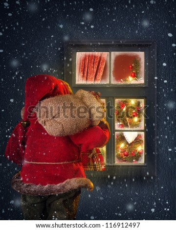 Santa Claus looking through a frosted window - stock photo