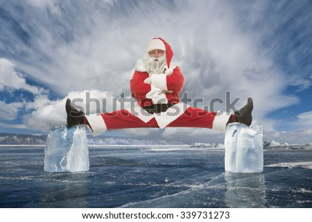 Santa Claus makes stretching between two ice cubes - stock photo