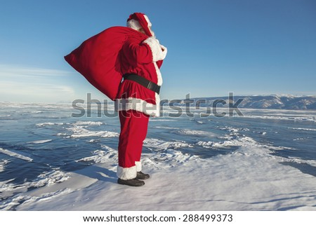 Santa Claus on ice of lake Baikal, shooting was conducted in a sunny day on lake Baikal - stock photo