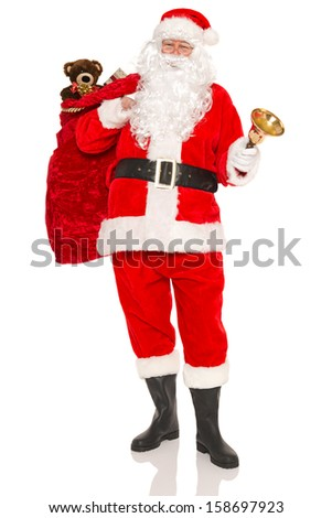 Santa Claus or Father Christmas carrying a sack full of gift wrapped presents and toys, isolated on a white background. - stock photo
