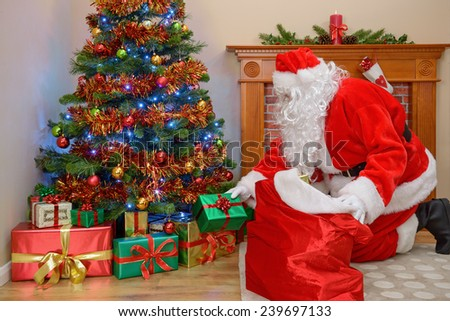 Santa Claus or Father Christmas putting gifts under the tree - stock photo
