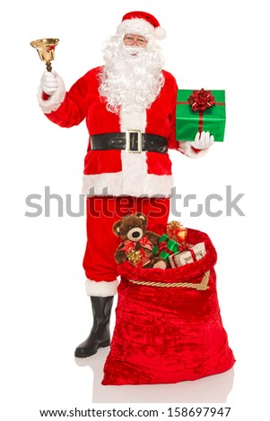 Santa Claus or Father Christmas with a sack full of gifts and holding a bell and green present, isolated on a white background. - stock photo