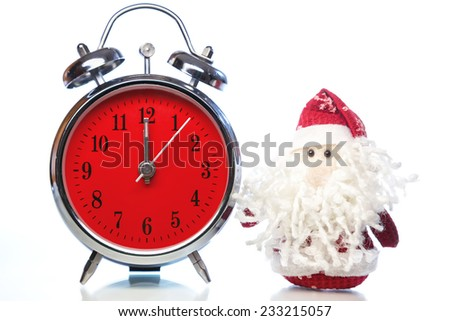 Santa Claus or Father Frost and vintage alarm clock with red dial on white background with reflection. Showing time twelve midnight - stock photo