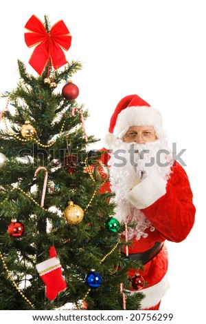Santa Claus peeking around the Christmas tree gesturing for you to be quiet. - stock photo