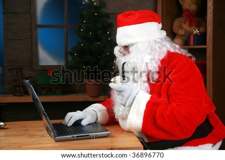 "Santa Claus points to his laptop computer, with ""room for your text"" - stock photo"