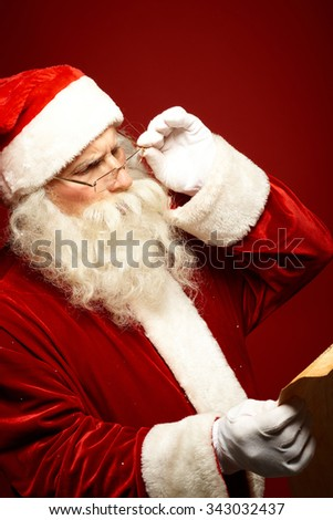 Santa Claus reading Christmas letter - stock photo