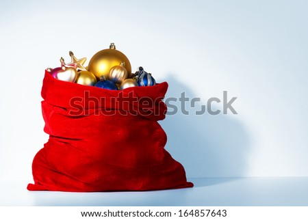 Santa Claus red bag with Christmas toys near the wall. File contains a path to isolation.  - stock photo