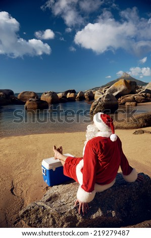 Santa Claus relaxing on the beach resting his bare feet on his cooler while looking at the view - stock photo
