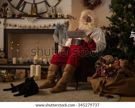 Santa Claus Resting at Home near Christmas Tree - stock photo