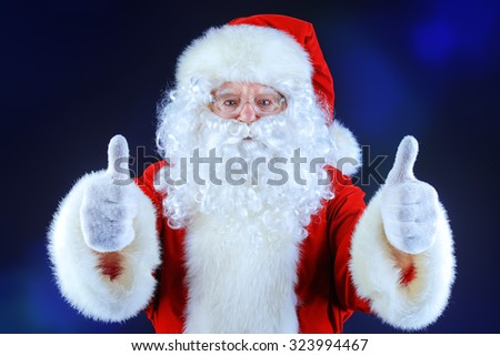 Santa Claus shows thumbs up over black background. Christmas time.  - stock photo