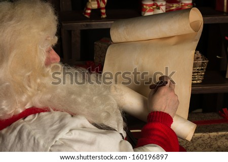 Santa Claus sitting at home and writing on old paper roll to do list with feather pen and ink at night with candle light. Authentic vintage style portrait. - stock photo