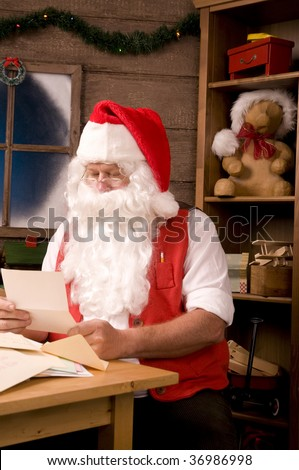 Santa Claus Sitting in His Workshop reading a letter. Vertical Composition. - stock photo