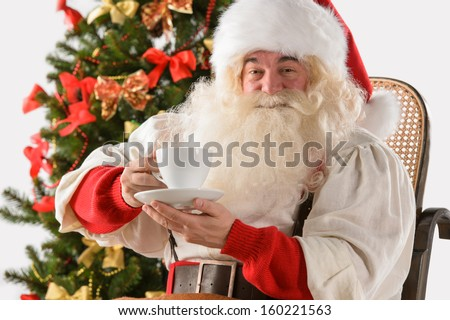 Santa Claus sitting in rocking chair near Christmas Tree at home and drinking hot tea or coffee - stock photo