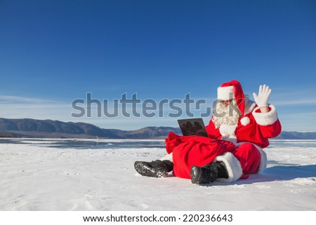 Santa Claus sitting on snow, looking at laptop news, shooting was conducted in a sunny day on lake Baikal - stock photo