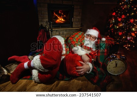 Santa Claus  sleeping at home near Christmas tree and  resting by his fireplace - stock photo