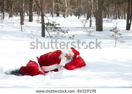 Santa Claus sleeping in winter wood - stock photo